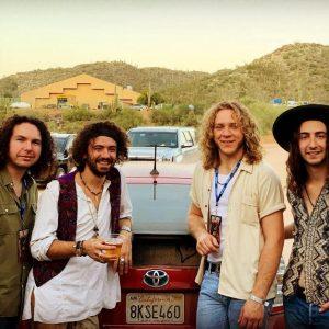 four men behind a truck